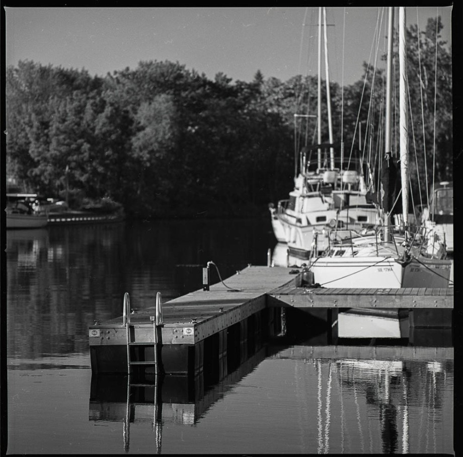 A dock with a sailboat in the background